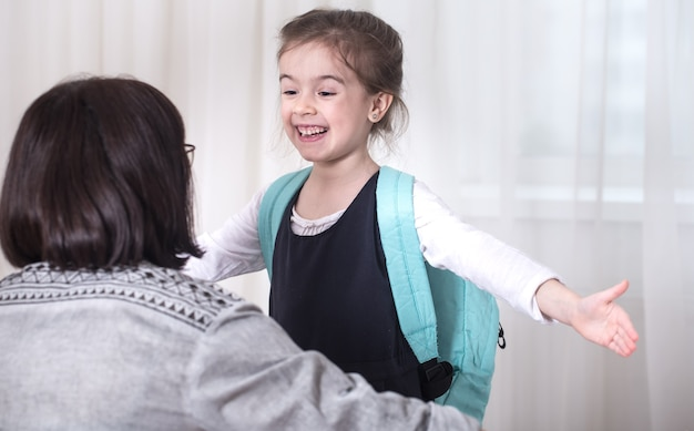 Ouder en meisje basisschool student knuffelen elkaar op een lichte achtergrond. terug naar school-concept