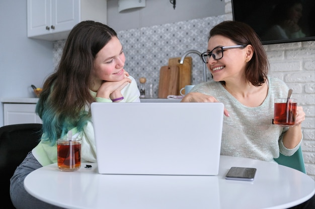 Ouder en tiener om thuis te zitten in de keuken en kijken naar laptop scherm