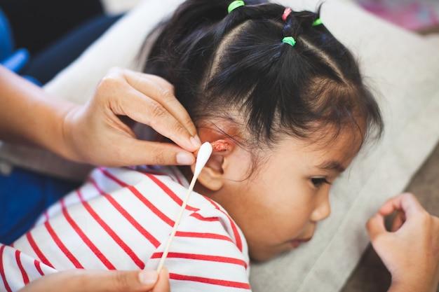 Ouder helpt haar kind bij het uitvoeren van een eerste hulp oorblessure nadat zij een ongeluk heeft gehad