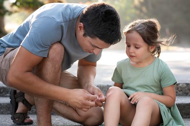 Ouder helpt zijn kind met knieblessure