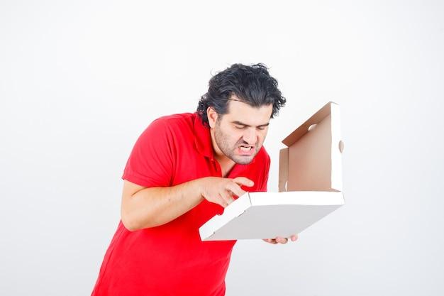 Ouder mannetje dat geopende pizzadoos in rood t-shirt bekijkt en hongerig kijkt. vooraanzicht.