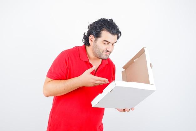 Ouder mannetje dat geopende pizzadoos in rood t-shirt bekijkt en verrukt kijkt. vooraanzicht.