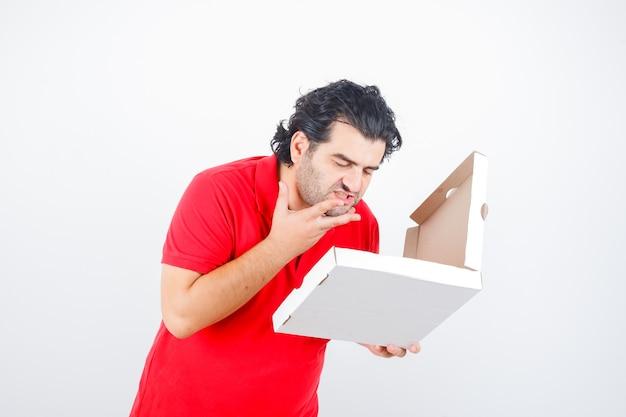 Ouder mannetje dat in rood t-shirt geopende pizzadoos bekijkt en hongerig, vooraanzicht kijkt.
