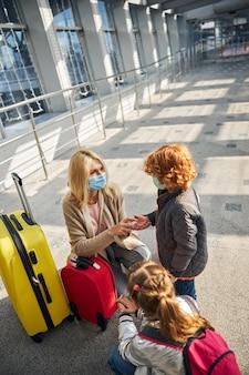 Ouder met een masker die wat antiseptisch middel aanbrengt op jongenshanden