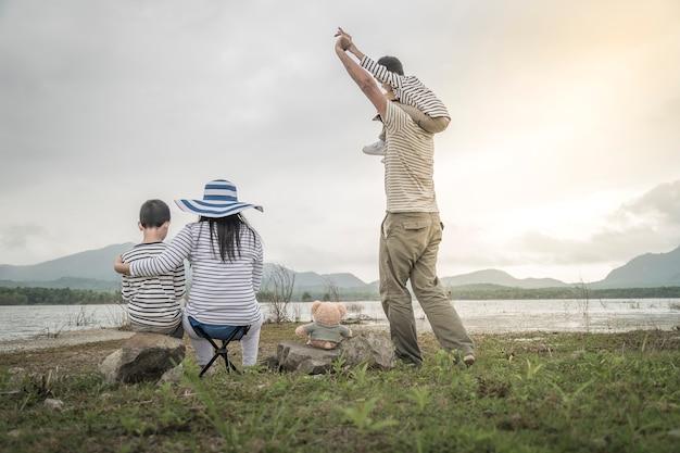 Ouder met jonge dochters en zoon op picknick in de buurt van het meer