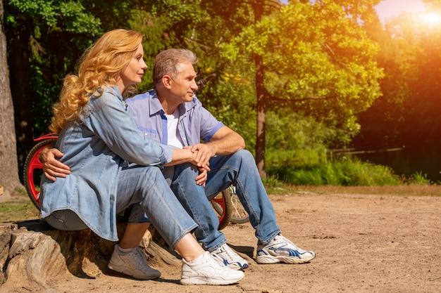 Ouder paar aan het meer met een fiets zitten in de zon