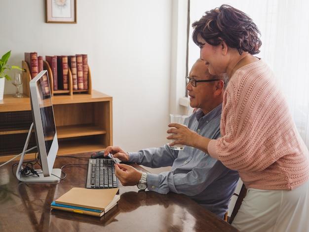 Ouder paar dat computer samen thuis met behulp van