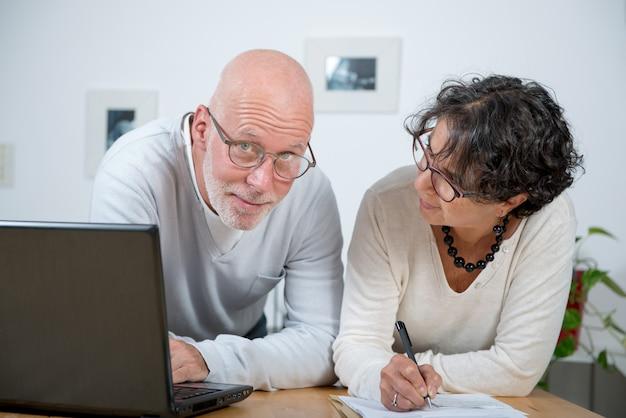 Ouder paar dat laptop met behulp van