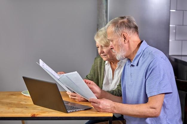 Ouder paar financiën thuis met behulp van laptop controleren, samen plannen van budget bespreken, met behulp van online bankdiensten en rekenmachine, documenten in de keuken houden