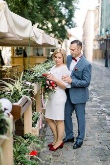 Ouder paar in modieuze kleding, poseren in de buurt van bloempotten decoraties in openlucht stadscafé