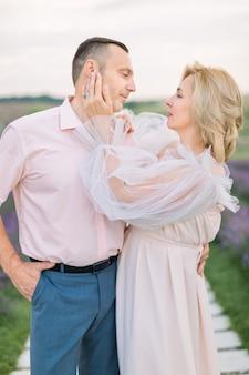 Ouder paar, kijken elkaar teder en liefdevol aan, staan samen in het lavendelveld