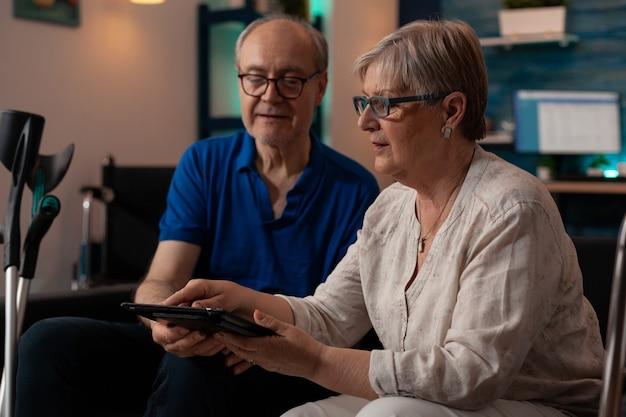 Ouder paar kijken naar moderne tablet in woonkamer