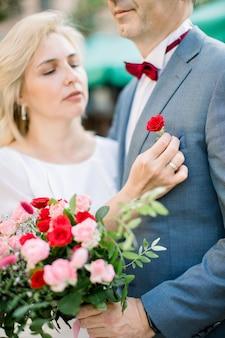 Ouder paar klaar voor de huwelijksceremonie, elkaar knuffelen