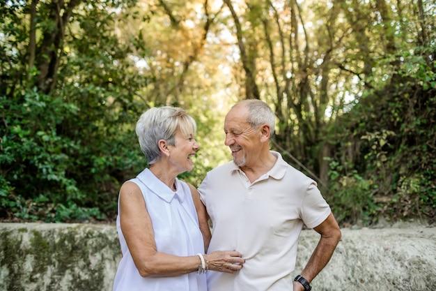 Ouder paar lachend op zoek in elkaars ogen verliefd tijdens een natuurwandeling.