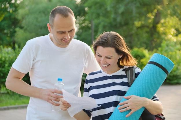 Ouder paar lezing document documentbrief. man en vrouw buiten in sportkleding met oefeningsmat. gezonde, actieve levensstijl van mensen van middelbare leeftijd.