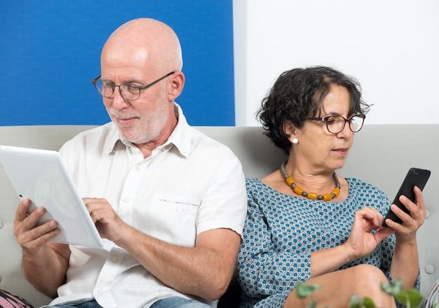 Ouder paar met behulp van smartphone en tablet