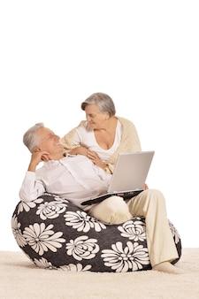 Ouder paar ontspannen thuis met laptop op een wit