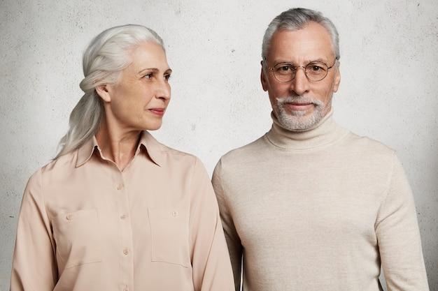 Ouder paar poseren tegen betonnen muur