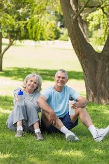 Ouder paar zitten met waterflessen in het park