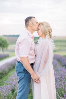 Ouder romantisch verliefde paar wandelen in lavendel veld. dromerig gelukkig kaukasisch echtpaar van middelbare leeftijd in de natuur, staande hand in hand. man die zijn vrouw kust. genieten van het moment.
