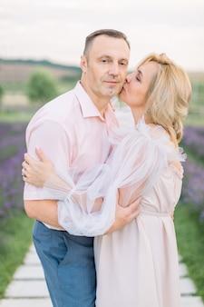 Ouder romantisch verliefde paar wandelen in lavendel veld. dromerig gelukkig kaukasisch echtpaar van middelbare leeftijd in de natuur, staande hand in hand. vrouw die haar man kust. genieten van het moment.