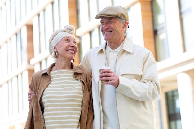 Ouder stel buiten in de stad met een kopje koffie