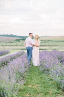 Ouder stel, dat hun huwelijksverjaardag viert, geniet van een moment van geluk en liefde, wandelend in een lavendelveld