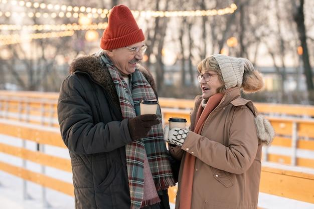 Ouder stel dat met elkaar praat en hete thee buiten drinkt tijdens hun winterwandeling