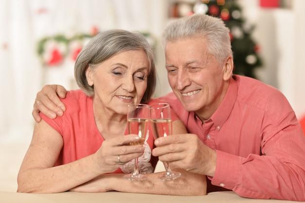 Ouder stel dat nieuwjaar thuis viert met champagne