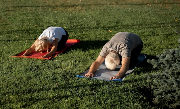 Ouder stel doet yoga buitenshuis