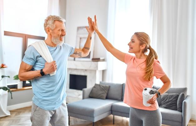 Ouder stel geeft vijf gebaren en doet thuis oefeningen en heeft plezier.