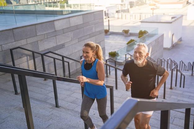 Ouder stel in sportkleding loopt een trap op in de stad terwijl ze samen aan het sporten zijn