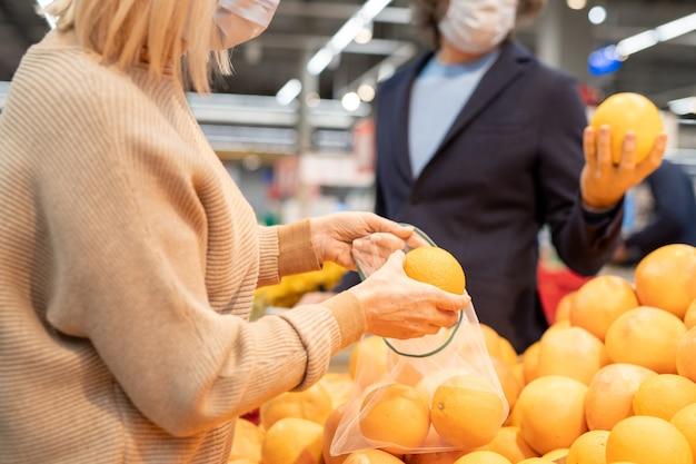 Ouder stel in vrijetijdskleding die verse rijpe sinaasappels of grapefruits kiest door te laten zien terwijl de vrouw er een in een fruitzak doet in de supermarkt