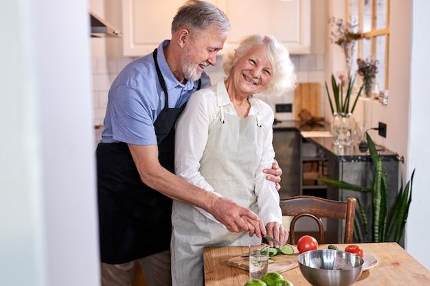 Ouder stel samen koken, vriendelijk getrouwd stel geniet van tijd doorbrengen in de keuken in het weekend