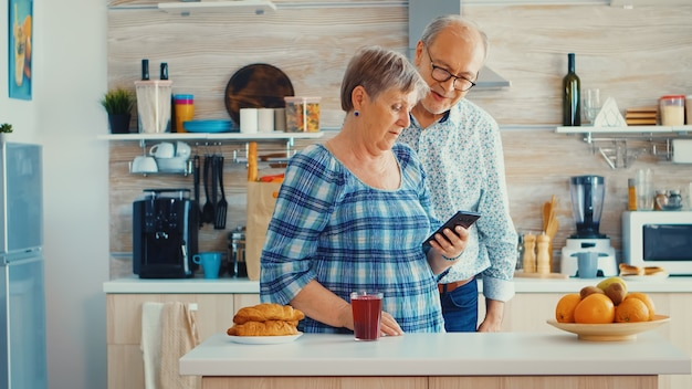 Ouder stel tijdens videochat met familie die smartphone in de keuken gebruikt. grootouders online gesprek. ouderen met moderne technologie op pensioengerechtigde leeftijd die mobiele apps gebruiken