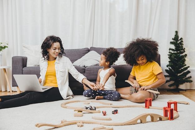 Ouder werkt thuis vanaf internet computer laptop effect van covid-19 virus pandemische ziekte gezonde moeder gelukkig leven om te blijven en met haar kinderen te spelen