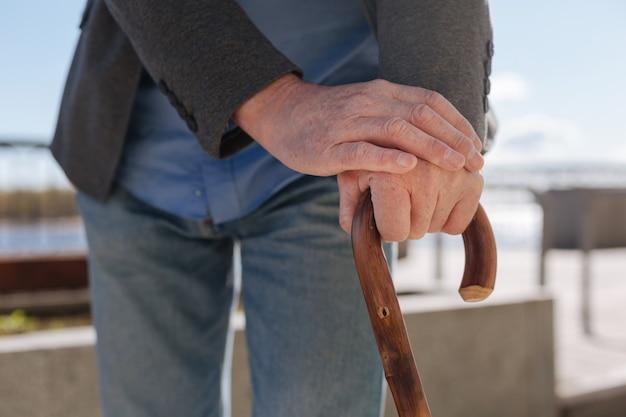 Ouder wordende geconcentreerde oude gepensioneerde die op de promenade staat en zijn handen op de stok legt en ontspant