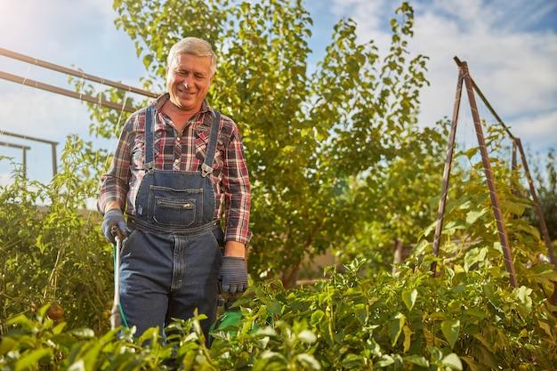 Ouder wordende man die lacht terwijl hij in zijn tuin werkt en zijn planten besproeit