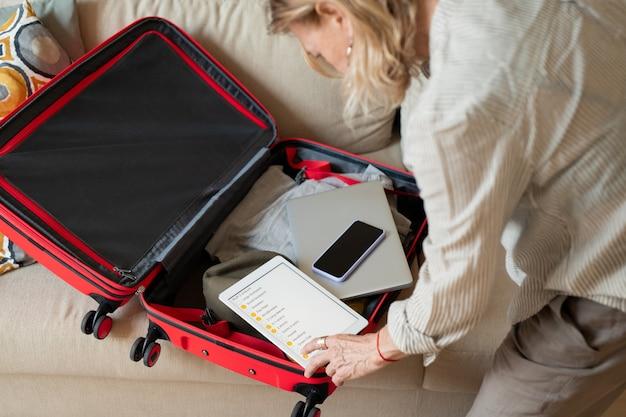 Ouder wordende vrouw kijkt door reislijst in digitale tablet zittend op de vloer en bukken open koffer met kleding en gadgets