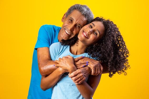 Oudere afro man knuffelen zijn schattige dochter op gele achtergrond. vaderdag
