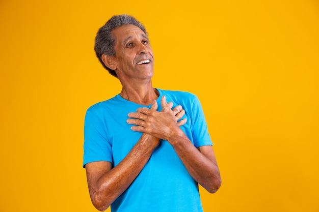 Oudere afro man met hand op borst dankbaar