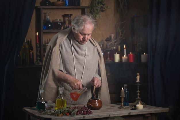 Oudere alchemist monnik brouwt toverdrank