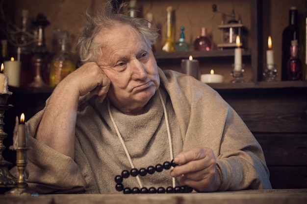 Oudere alchemist monnik met rozenkrans