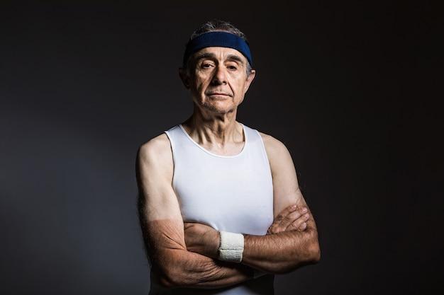 Oudere atleet met een wit mouwloos shirt, met zonmarkeringen op de armen en een blauwe hoofdband met gekruiste armen, op een donkere achtergrond. sport en overwinning concept.