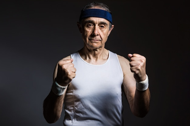 Oudere atleet met een wit mouwloos shirt, met zonnevlekken op de armen en een blauwe hoofdband die zijn vuisten balt, op een donkere achtergrond. sport en overwinning concept.