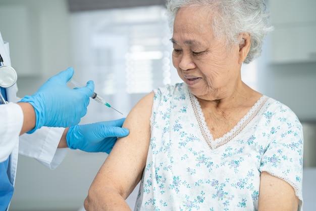Oudere aziatische senior vrouw met gezichtsmasker die coronavirusvaccin krijgt door arts, maakt injectie