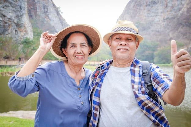 Oudere aziatische stellen trekking high mountain geniet van het leven na hun pensionering