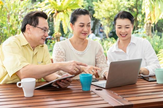 Oudere aziatische vrienden die laptops en tabletten in verpleeghuis gebruiken.