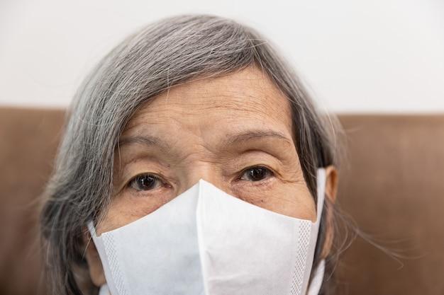 Oudere aziatische vrouw die recht naar de camera kijkt met een gezichtsmasker.