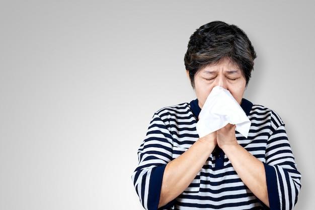Oudere aziatische vrouw heeft griep en niezen van ziekte seizoensgebonden virus probleem